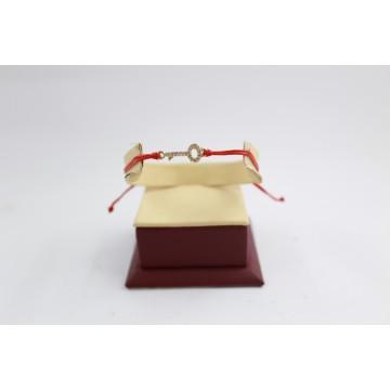 Златна регулираща се гривна с червен конец и ключ 3103